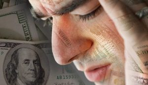 man with headache over money background